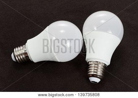 Two energy-saving LED light bulb on black fabric