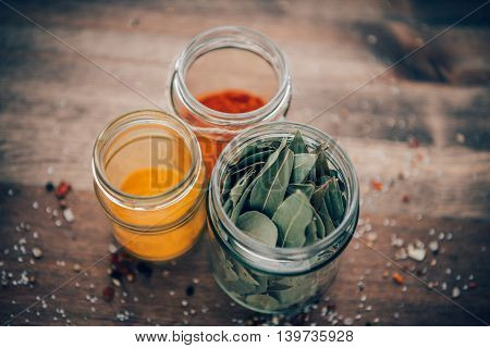 Spices In Jars On A Wooden Table.
