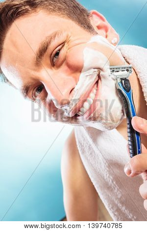 Happy smiling man shaving using razor with cream foam. Handsome guy removing face beard hair. Skin care and hygiene.