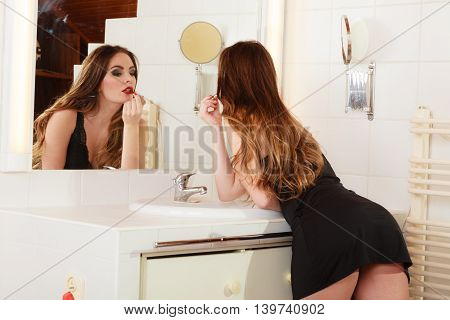 Sexy girl making makeup in bathroom. Woman take care about look. Looking into a mirror.