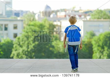 Boy with backpack on city street. Back to school education knowledge people travel tourism leisure concept