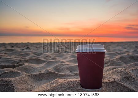 Close up plastic bracing and restorative coffee cup on sand beach and view of sunset or sunrise background, peaceful