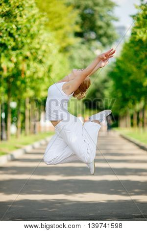 Happy Caucasian young woman jumping in park on summer day