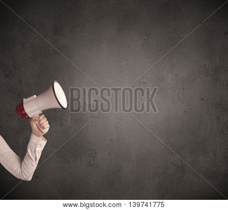 Caucasian arm holding megaphone with plain grunge background