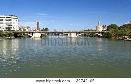 SEVILLE, SPAIN - September 13, 2015: View of the Torre del Oro and the Bridge of San Telmo crossing the Guadalquivir River on September 13, 2015 in Seville, Spain