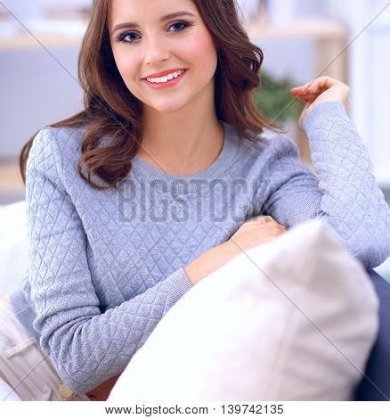 Portrait of happy young woman sitting on sofa.