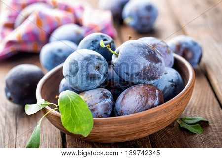 fresh plums with leaves in a bowl on wooden table