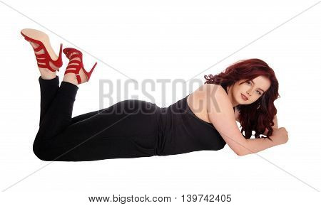 A pretty young woman in a black jumpsuit lying on the floor on her stomach with long red hair isolated for white background.