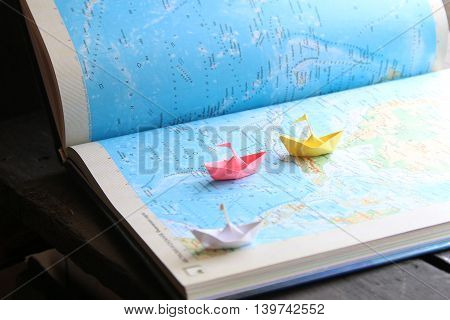 Travel or vacation idea, paper boats on the map