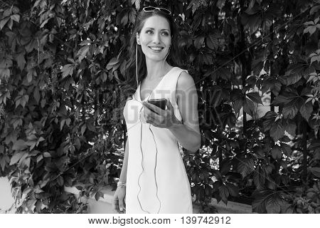 Black-and-white romantic image of cute smiling young lady with player