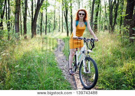 Young ginger woman in sunglasses riding a bike on a path in the forest
