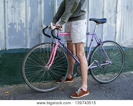 Man in shorts carrying the bike against the wall