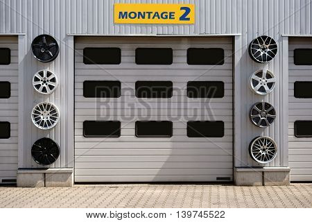 A garage with several garages and sport rims for decoration.