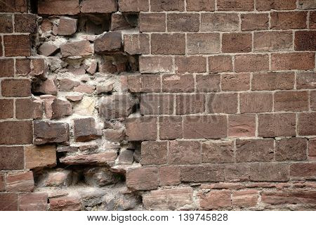 A wall of distinctive red bricks with damage and holes.