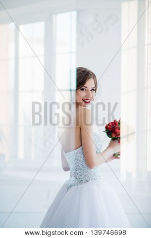 young and beautiful fashion art photo of a bride in white dress in living room. Shot through the glass, light creative reflections overlay portrait of hers