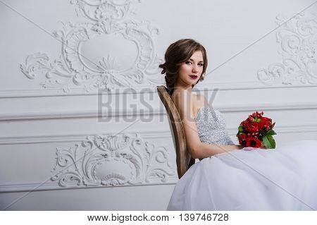 Young beautiful bride sitting on vintage chair. The Studio is all white. Antique wall with stucco mouldings on the background.