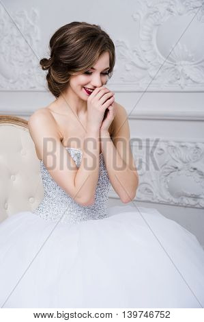 Gorgeous adorable brunette in wedding dress over luxury interior