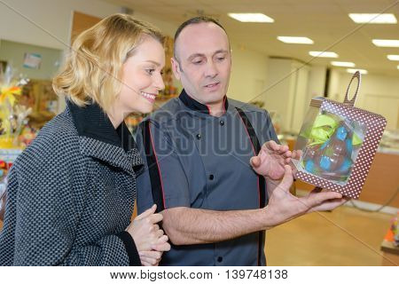 confectionery employee showing chocolate bunny to female client