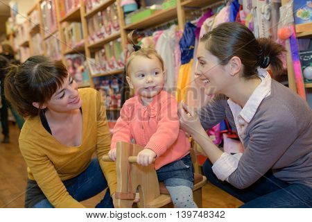 mother and her friend shopping with daughter in toy store