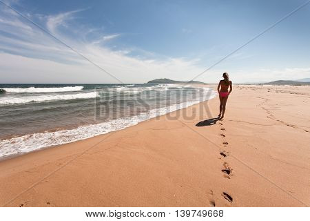 Young woman goes the distance through the empty wild beach against a blue sky yellow sand and sea. Wide angle.