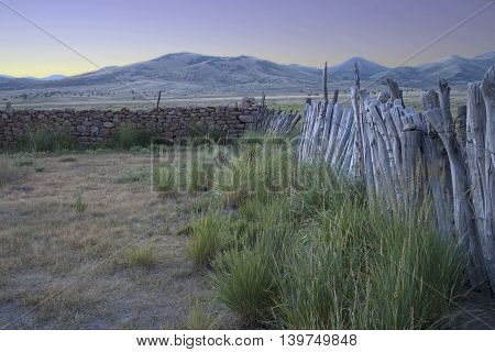 Sunrise over an old wooden fence leading to a rock wall on and abandoned homestead in the mountains of Central Nevada.