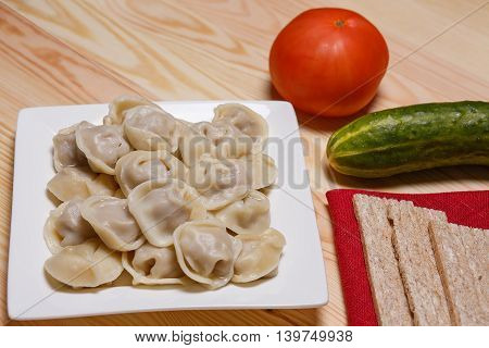 Plate with pelmeni and a fork on a wooden table. A cucumber, tomato, a paprika and mustard on a table. Red napkin.