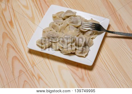 Plate with pelmeni and a fork on a wooden table.