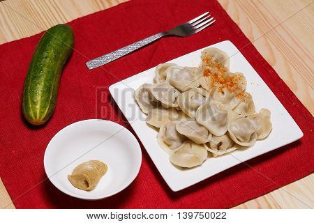 Plate with pelmeni and a fork on a wooden table. A cucumber, a paprika and mustard on a table. Red napkin.