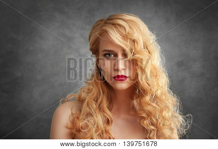 Portrait of young woman with blonde hair on grey background