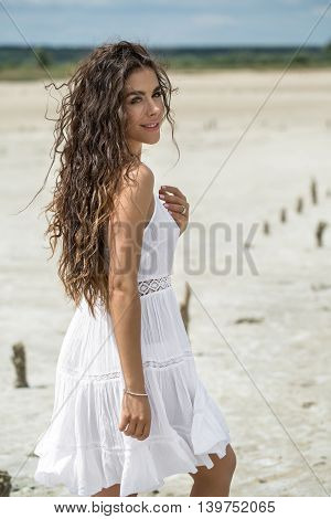 Smiling girl stands sideways on the sand on the nature background. She wears white dress. She holds right arm along the body, left hand is on the chest. She looks into the camera. There are wooden pillars on the sand behind the girl. Outdoors. Vertical.