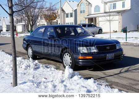 JOLIET, ILLINOIS / UNITED STATES - NOVEMBER 24, 2015: A blue Lexus LS-400 luxury sedan is parked in a residential area of Joliet after a November snowstorm.