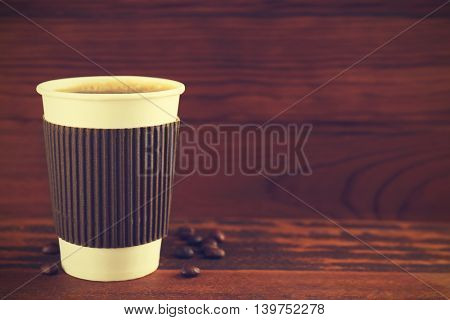 Paper cup of coffee on wooden background