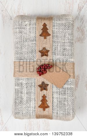 Fabric wrapped Christmas gift on a rustic wood table. Vertical format from a high angle.