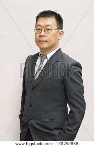 A stern looking asian business man standing