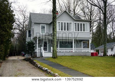 WEQUENTONSING, MICHIGAN / UNITED STATES - DECEMBER 23, 2015: A two-story home, christened Northome, with a front porch and a driveway on Beach Drive in Wequetonsing.