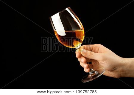 Male hand holding glass of wine on black background