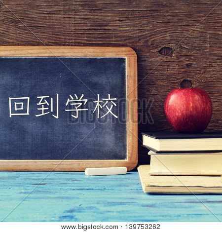a chalkboard with the text back to school written in Chinese, a piece of chalk and an apple on a pile of books, placed on a blue wooden desk, against a rustic wooden background