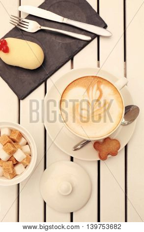 Delicious composition with cappuccino and cake on light wooden table