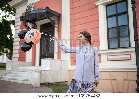 Beautiful young brunette woman in a long purple dress walking the streets of Odessa, Ukraine. Bahram develops during gait. In the hands of a balloon with a picture of Mickey Mouse.