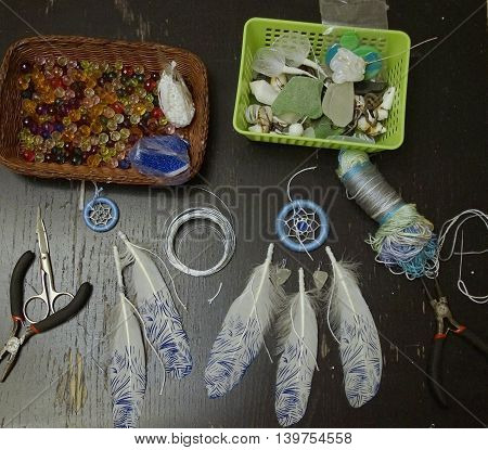photo of a the process of creating handmade dreamcatcher with white printed feathers, different glass beads, pliers, thread, scissors and wire
