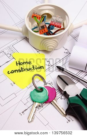 House of yellow paper home keys work tools and cable connections in electrical box lying on construction drawing of house concept of building home