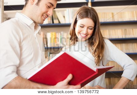 Couple reading a book in a library