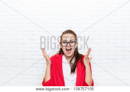 Excited businesswoman happy smile wear red jacket glasses business woman over office wall
