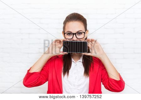Businesswoman show cell smart phone screen with empty copy space wear red jacket glasses business woman over office wall