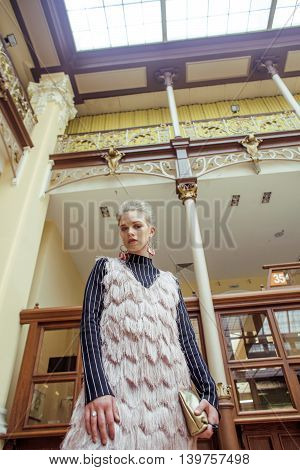 young attractive fashion lady on railway station waiting, vintage people concept in classic interior