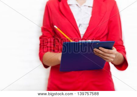 Businesswoman hold folder pencil write wear red jacket business woman over office wall