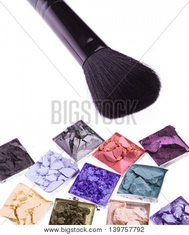 multicolored crushed eyeshadows with brush isolated on white background