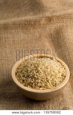 Natural brown uncooked rice in wooden bowl on burlap sack