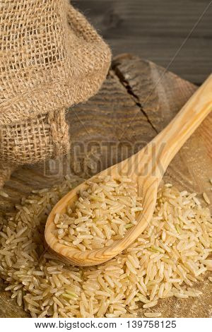 Natural brown uncooked rice in wooden spoon on wood table