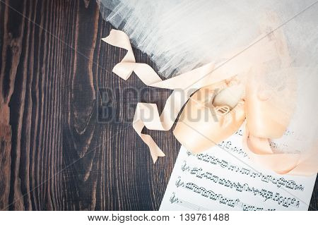 Ballet shoes skirt and music sheet on a wooden background